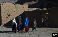 Hazara women walk along a road in Bamiyan Province, where they have more freedom than the Taliban would allow.