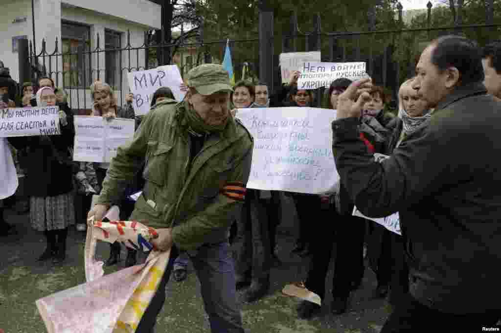 Aqmescitte çarşenbe künü martnıñ beşinde genç qızlar Ukraina Silâlı Quvetleriniñ arbiy hızmetçilerine Ukraina Arbiy-deñiz quvetleri yalı mudafaa ordularınıñ ştabı yanında qol tutuv numayışına çıqtılar