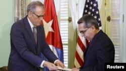 رئیس هیئت نمایندگی آمریکا در هاوانا در حال تسلیم نامه اوباما به وزیر خارجه موقت کوبا