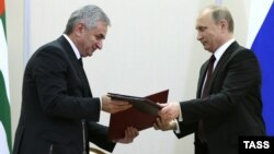 Abkhazian leader Raul Khajimba (left) and Russian President Vladimir Putin exchange documents during the signing ceremony at the Bocharov Ruchei residence in Sochi on November 24.