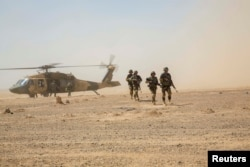 Afghan National Army 215th Corps troops disembark an Afghan Air Force Black Hawk helicopter.