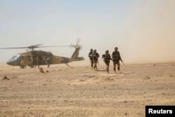 Ооганстандын коопсуздук күчтөрү Black Hawk тик учагынан түшүүдө.