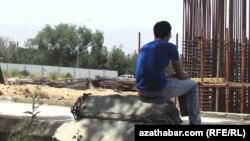 Türkmenistandaky gurluşyk sebitleriniň birinde oturan işçi.
