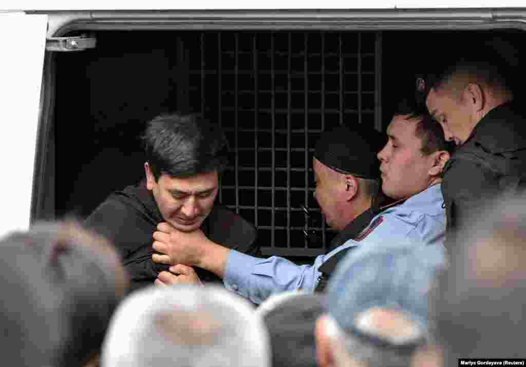 Полиция ұсталғандарды күштеп көлікке салып жатыр. Алматы, 9 маусым 2019 жыл.