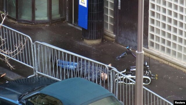 French police use a bomb-disposal robot to inspect the body of a man shot dead outside a police station in Paris.