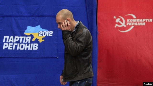 A man walks past the ruling Party of Regions (left) and Communist Party election campaign tents in Kyiv last week.