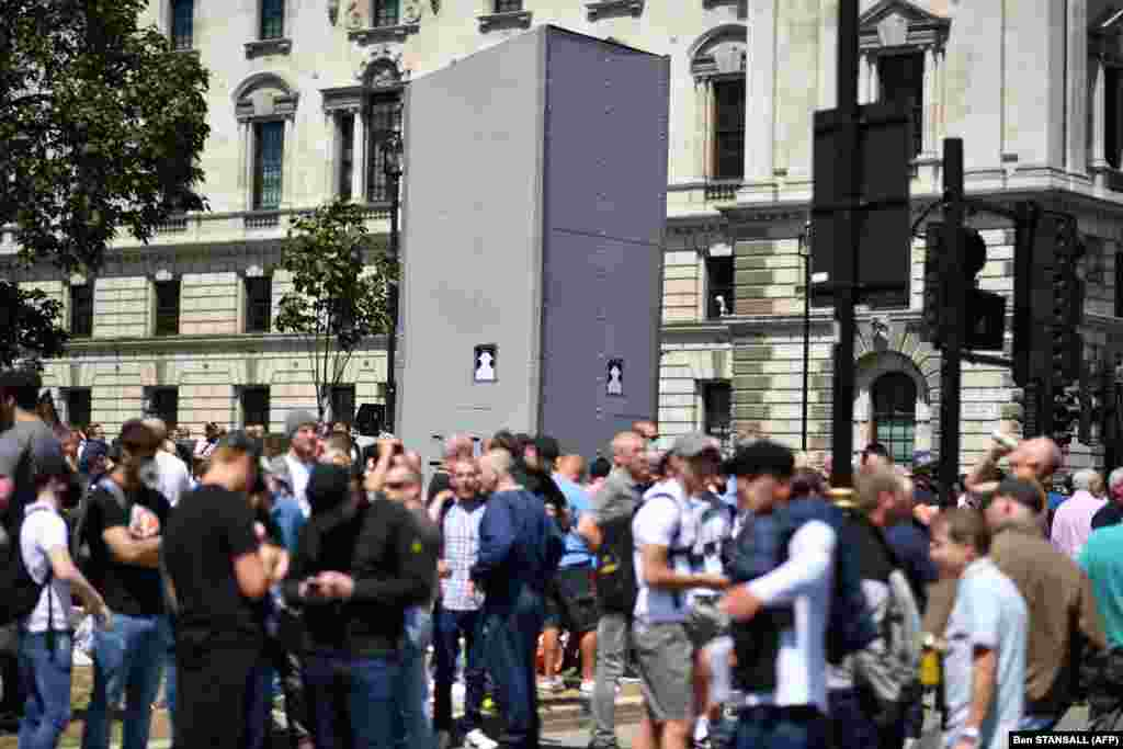 Members of far right groups gather around the boarded-up statue of Winston Churchill in Parliament Square in central London on June 13, 2020. ​Various right-wing groups and soccer fans came to London, saying they wanted to guard historical monuments that have been targeted in the past week by anti-racism protesters.