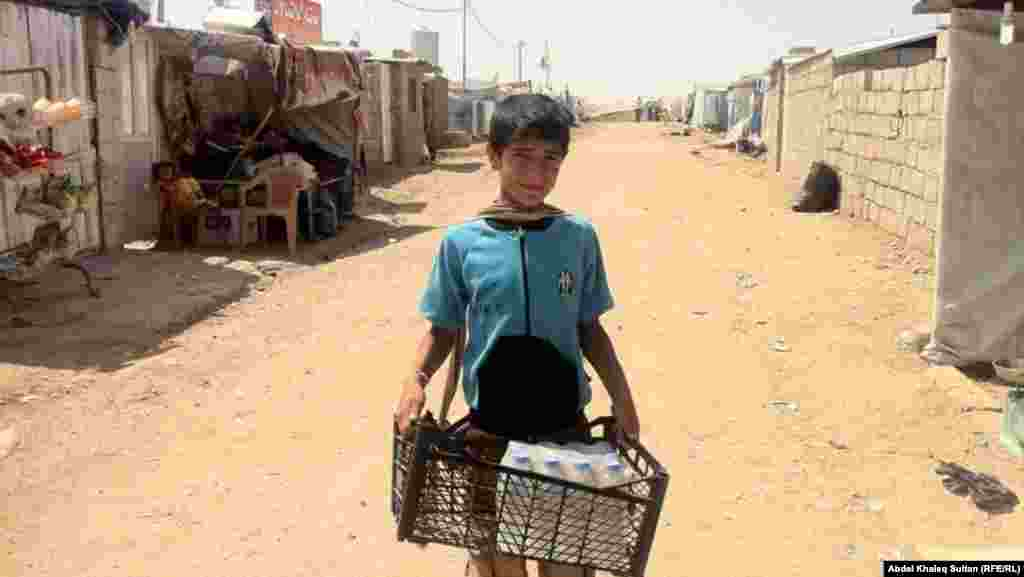 Part of an earlier wave of refugees, a child carries supplies at the Domeez refugee camp in Iraq's Duhok Province on July 4.