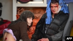 Two people sit in an ambulance waiting to be treated after a rocket slammed into a shopping mall in Donetsk's Kubishevski district on October 8.
