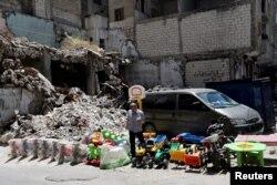 Мужчина продает детские игрушки на фоне руин разрушенных зданий в городе Идлиб. 25 мая 2019 года