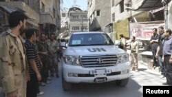 Syria - Free Syrian Army fighters and residents gather around a convoy of U.N. vehicles carrying a team of United Nations chemical weapons experts at one of the sites of an alleged chemical weapons attack in Damascus' suburbs of Zamalka August 28, 2013