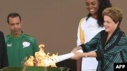 Президент Бразилии Дилма Руссефф вручает олимпийский факел бразильской волейболистке Фабиано Клаудино