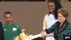Президент Бразилии Дилма Руссефф вручает олимпийский факел бразильской волейболистке Фабиано Клаудино. Бразилиа, 3 августа 2016 года.