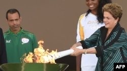 Президент Бразилії Ділма Руссеф (п) тримає олімпійський факел перед початком його подорожі містами країни, 3 травня 2016 року