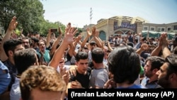 IRAN -- A group of protesters chant slogans at the main gate of the Old Grand Bazaar, in Tehran, June 25, 2018