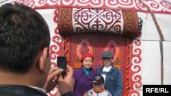 Семья фотографируется на фоне юрты во время празднования Наурыза. Алматы, 22 марта 2009 года.