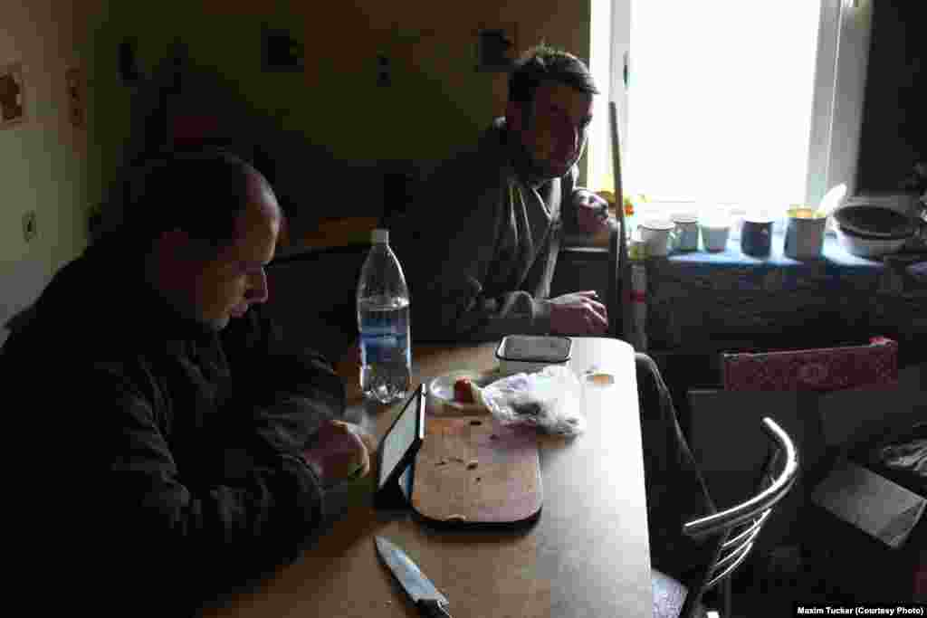 Viktor (left) and Vova take a break from the fighting at a command post in Pisky. Viktor has been fighting for less than a month, while Vova is expecting demobilization after serving a 14-month tour.  April 3, 2016