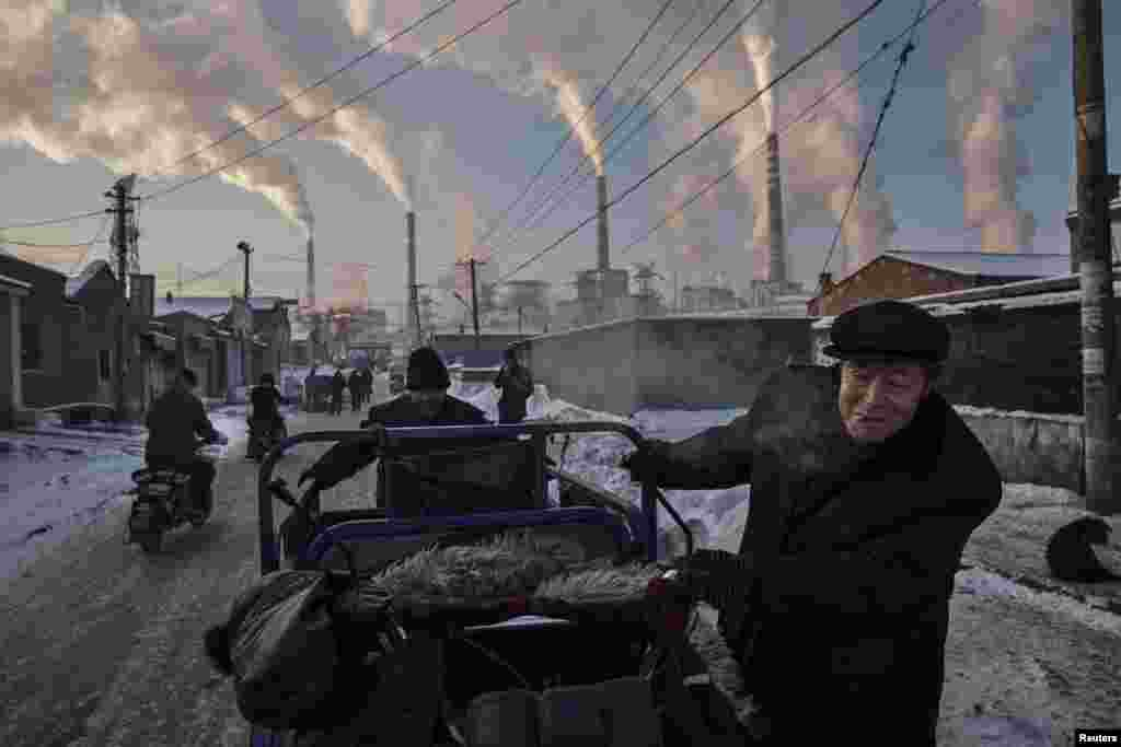 First Prize Singles in the Daily Life category was won by Getty Images' Kevin Frayer. Chinese men pull a tricycle in a neighborhood next to a coal-fired power plant in Shanxi, China. (November 26, 2015)