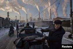 Местные жители возле угольной электростанции в провинции Шаньси, Китай. Иллюстративное фото.