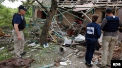 OSCE observers inspect a private building that was destroyed by shelling in Avdiyivka last month.