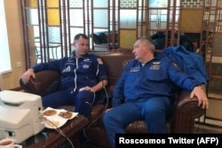 Roskosmos chief Dmitry Rogozin (right) sits next to NASA astronaut Nick Hague as he undergoes a medical examination in Zhezqazghan after the aborted flight.