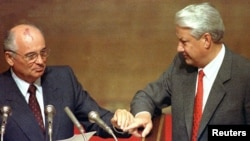 Russian President Boris Yeltsin (right) and Soviet President Mikhail Gorbachev touch hands during Gorbachev's address to the extraordinary meeting of the Supreme Soviet of the Russian Federation in Moscow in August 1991.