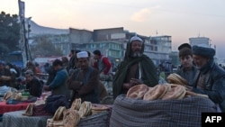 Afghan vendors wait for customers at a busy market on a cold day in Kabul on November 19.