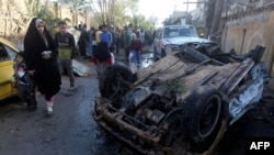 Iraqis gather at the site of a car bombing in the Shuala area of Baghdad on January 30.