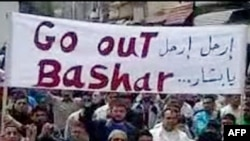 "A YouTube video grab shows antigovernment protesters holding a banner that reads in Arabic and English ""Go Out Bashar"" during a pro-democracy demonstration after Friday Prayers in Tal Kalakh on June 10."