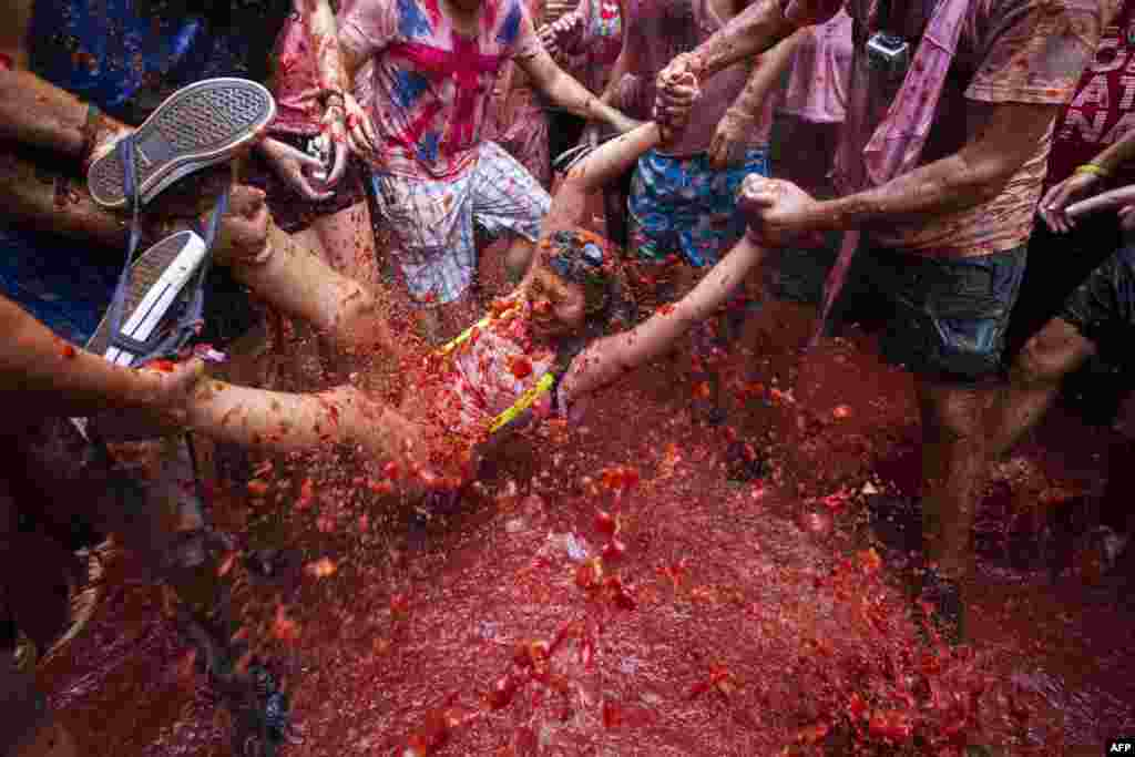 "Revelers take part in the annual ""Tomatina"" festivities in Bunol, near Valencia, Spain. Some 20,000 participants hurled 130 tons of squashed tomatoes at each other, drenching the streets in red. (AFP/Gabriel Gallo)"