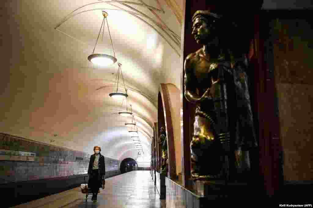 Мәскеу метросында маска таққан жолаушы кетіп барады.