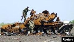 """Представители самопровозглашенной """"Донецкой народной республики"""" осматривают останки танка в аэропорту города Донецка, 22 мая 2015 года."""