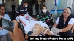 Саҳнаи кӯмак Кӯмак ба навресе, ки дар ҳамлаи мусаллаҳона BRAZIL -- A teenager who was injured during a shooting inside the Raul Brasil State School, is carried on a gurney into a hospital, in Suzano, March 13, 2019