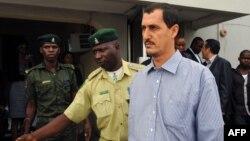 Reputed Iranian Revolutionary Guards Corps member Azim Aghajani (right) is led away after his conviction for illegal arms trafficking in the Federal High Court in Lagos on May 13.