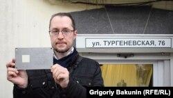 Табличка в руках инициатора установки памятного знака Григория Тарасенко