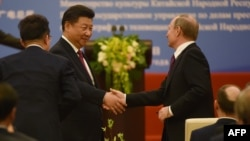 Chinese President Xi Jinping (left) shakes hands with Russian President Vladimir Putin during a ceremony marking the 15th anniversary of the signing of the China-Russia Treaty on Good Neighborliness, Friendship, and Cooperation, in Beijing's Great Hall of the People on June 25.