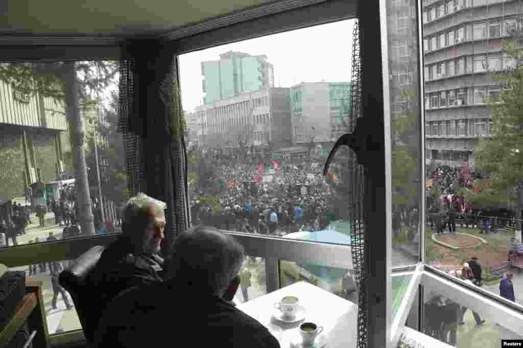 People at a cafe watch a protest organized by the opposition movement Vetevendosje (Self-Determination) in Mitrovica on March 20. Thousands marched to protest against the planned talks between Kosovo and Serbia.
