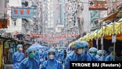 Védőruhás egészségügyi dolgozók Hongkong egy, a koronavírus miatt lezárt negyedében, 2021. január 23-án.