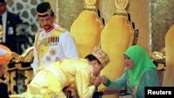 Sultan Hassanal Bolkiah (solda), böyük oğlu, Şahzadə Al-Muhtadee Billah (ortada) və kraliça Hajjah Maniam, arxiv fotosu