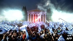 Supporters of the leader of the conservative party New Democracy, Antonis Samaras, wave flags during a pre-election speech in Athens.