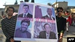 """Siriýanyň Kfar Nubul şäherçesinde protestçiler """"Çagalaryň ganhorlary"""" diýlen ýazgyly plakaty göterip durlar. 27-nji maý, 2012."""