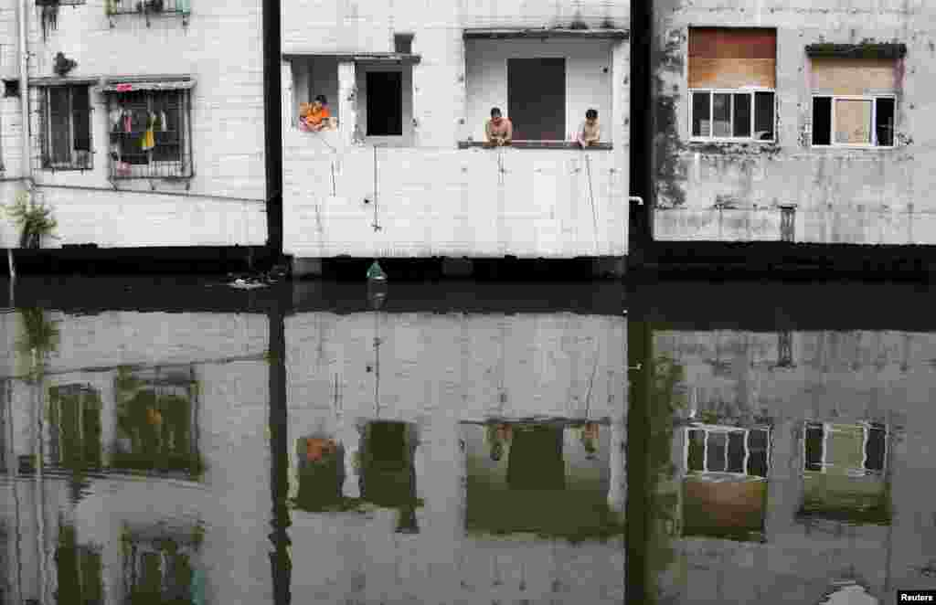 People fish at an abandoned flat in Xian village, a slum area in downtown Guangzhou, China. (Reuters/​Tyrone Siu)