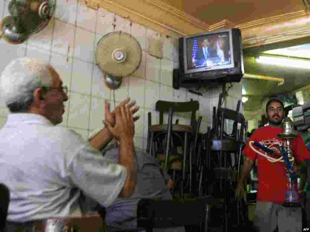 "EGYPT, Cairo : An Egyptian man (L) applauds as he listens to US President Barack Obama's speech at Cairo University, at a coffee shop in Cairo on June 4, 2009. Egyptians across the social spectrum hailed Obama's ""historic"" speech to the world's Muslims, while looking forward to assertive actions in the Middle East."