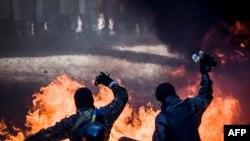 Участники антиправительственных протестов бросают камни в сторону милиции. Киев, 18 февраля 2014 года.