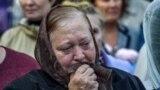 Женщина плачет на церемонии прощания с погибшими в Керченском политехническом колледже