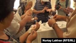 Люди в здании филиала президентской партии «Нур Отан» делают на пальцах небольшие надрезы, чтобы пометить письмо каплями крови. Алматы, 29 августа 2016 года.