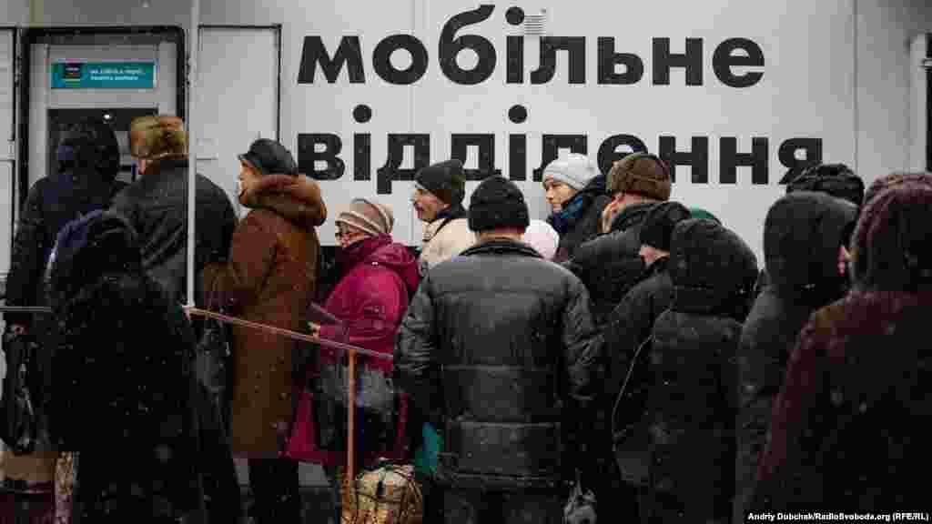 Мешканці з непідконтрольних Україні територій у черзі до мобільного пункту банкоматів«Ощадбанку» на КПВВ у Станиці Луганській, 4 січня 2018 року ПЕРЕГЛЯНЬТЕ ВІДЕО