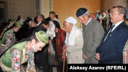 Kazakhstan – Kazakh Girls hand presents to elders, former classmates of Nazarbaev. Almaty, 20Dec2013