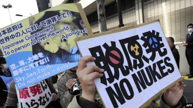 Protesters hold placards while marching in front of Tokyo Electric Power Company headquarters during a rally in the Japanese capital today.