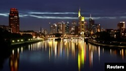 Поглед на карактеристичните банкарски кули во центарот на Франкфурт и нивниот одраз во реката Мајна